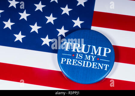London, UK - November 20th 2018: Trump Is My President pin badge, pictured over the flag of the United States of America. - Stock Photo