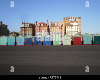 colorful little beach huts in front villas on the promenade in the sunlight in the english city of brighton - Stock Photo