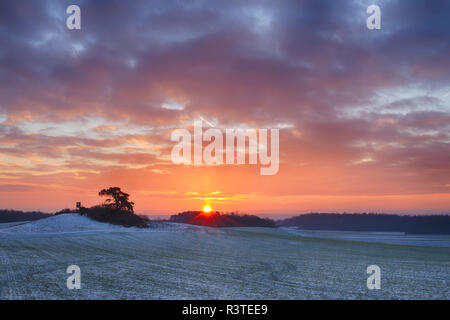 Germany, Bavaria, Sunrise over rural landscape with fields and forest in winter - Stock Photo