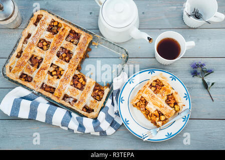 Homemade apple tart on plate and cup of black tea - Stock Photo