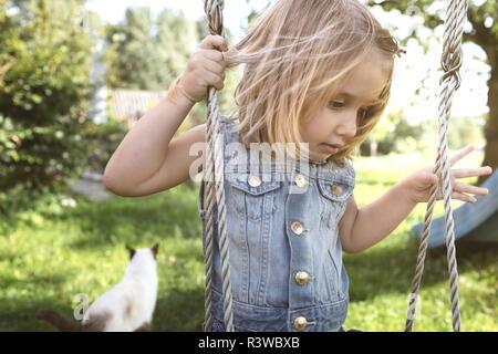 Little girl sitting on swing in the garden - Stock Photo