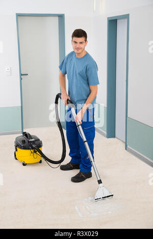 Male Cleaner Vacuuming Floor - Stock Photo