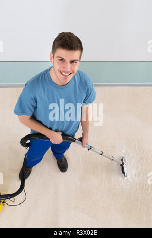 Male Janitor Vacuuming Corridor - Stock Photo