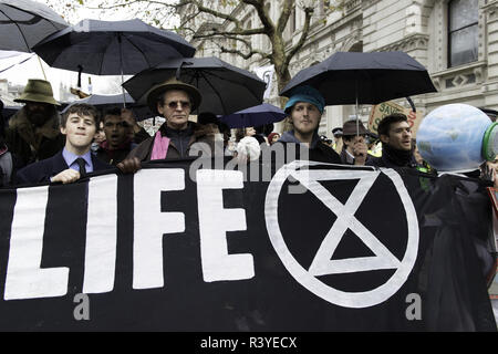 London, Greater London, UK. 24th Nov, 2018. Activists seen carrying a banner during the march.Thousands of demonstrators from the new Extinction Rebellion climate change movement gathered at Parliament Square for a memorial and funeral march through London. Demonstrators paid homage to the lives lost due to climate change, and marched carrying a coffin from Parliament Square to Buckingham Palace. Credit: Andres Pantoja/SOPA Images/ZUMA Wire/Alamy Live News - Stock Photo