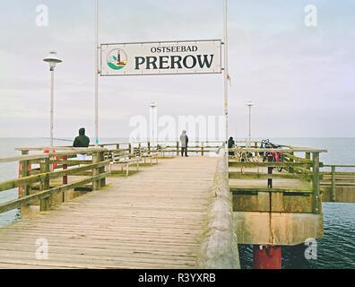 Prerow, Germany January 25 2018: Fishers on sea bridge fishing in Baltic sea.  Cold overcast day. - Stock Photo