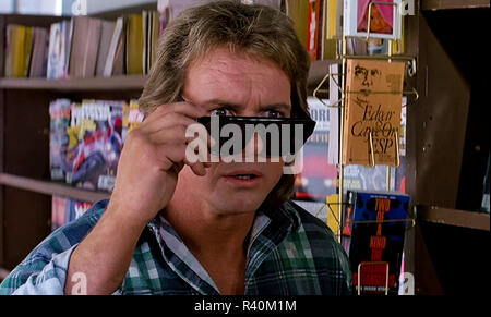 Nada tries on the Hoffman lenses and sees reality for the first time, from They Live (1988) directed by John Carpenter. An unnamed drifter finds a pair of sunglasses that reveal the truth of the world and how it manipulates and rewards its inhabitants. - Stock Photo