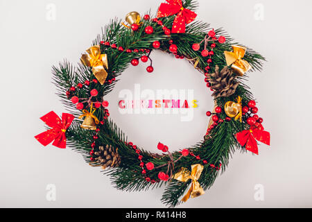 Christmas wreath with decoration on white background. Christmas title made of colorful wooden letters inside - Stock Photo