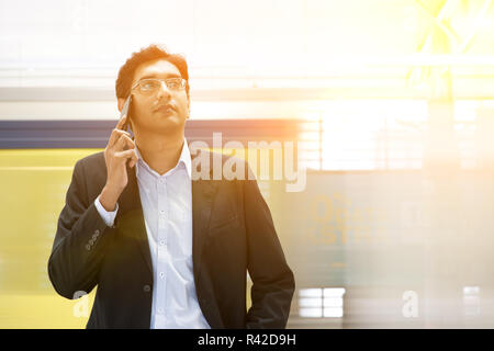 Indian businessman on the phone at railway station. - Stock Photo
