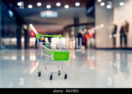 A small green toy cart in a large shopping Mall. The concept of shopping and sales in supermarkets.. Blur shopping cart in superstore. - Stock Photo
