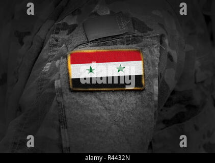Syrian flag on soldiers arm (Collage). - Stock Photo