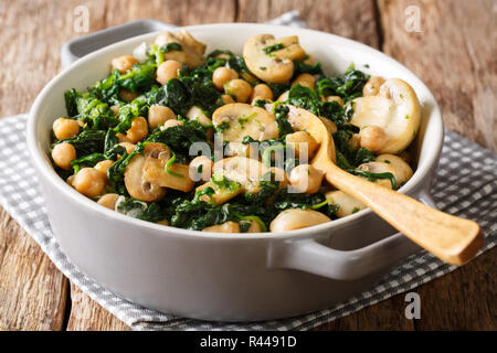 Cooked diet chickpeas with spinach and champignons close-up in a bowl on the table. horizontal - Stock Photo
