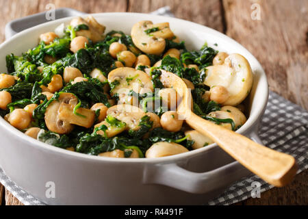 Healthy vegetarian food of chickpeas with spinach and mushrooms close-up in a bowl on the table. horizontal - Stock Photo