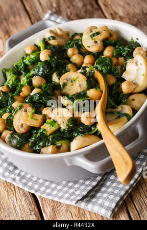 Stew of chickpeas with spinach and mushrooms close-up in a bowl on the table. vertical - Stock Photo