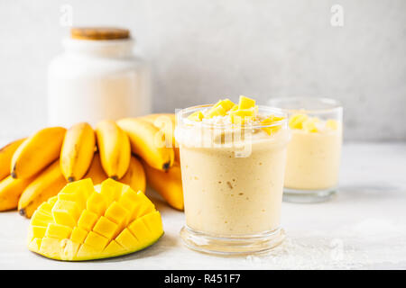 Mango banana smoothie with coconut in a jar. Plant based food concept. - Stock Photo