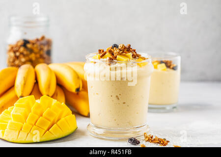 Mango banana smoothie with granola and coconut in a jar. Plant based food concept. - Stock Photo