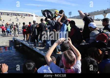 Tijuana, Mexico. 25th Nov, 2018. Groups of people try to cross El Chaparral, in the city of Tijuana, in the state of Baja California, Mexico, 25 November 2018. A group of migrants from the caravan of Central Americans who advanced today towards the San Ysidro (USA) gateway deviated from the planned route to try to cross the border wall by other points, while the US border police threw tear gas . Credit: EFE News Agency/Alamy Live News - Stock Photo