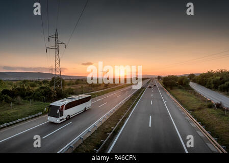 Bus traveling on a lonely countryside Highway with beautiful sunset behind - Stock Photo