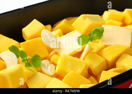 diced pumpkin with butter and garlic in a baking pan - Stock Photo