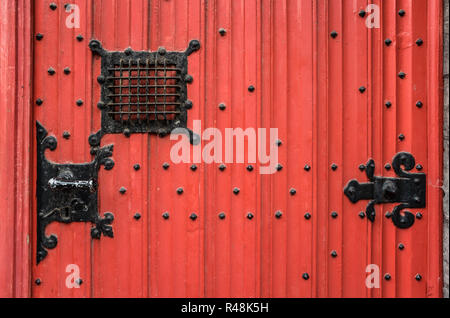 old,red wooden door with fittings on a house in brugge,belgium - Stock Photo