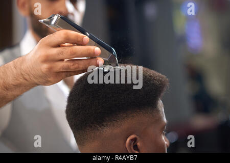 Closeup of process of trimming of hair in barber shop. Qualified barber keeping clipper in hands and correcting shape of hair to male client sitting on chair. Concept of haircut and shaving. - Stock Photo