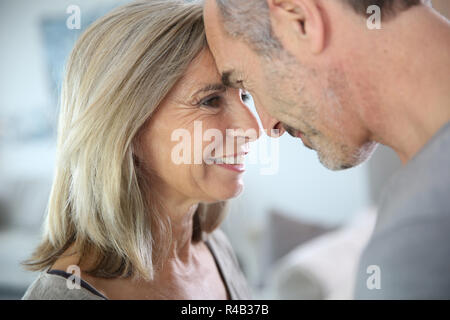 Loving senior couple looking at each other's eyes - Stock Photo