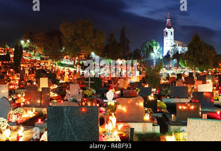 Cemetery at night with many graves and church - Stock Photo