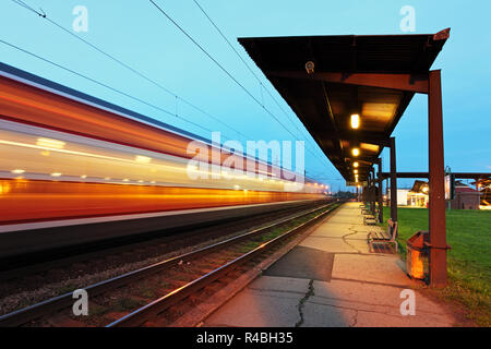 Passanger station with motion train at night - Stock Photo