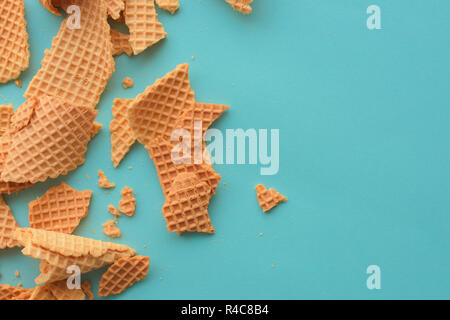 Crushed ice cream waffle cones on pastel blue background, top view flat lay modern minimal composition - Stock Photo