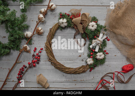 Top view of stages of making Christmas wreath with fir branches and decorative toys on wooden rustic tabletop - Stock Photo