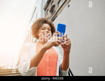 happy african woman with smartphone in city - Stock Photo