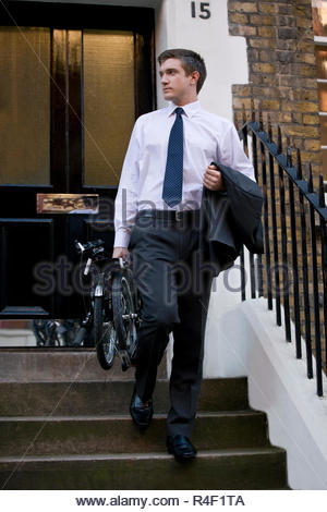 A businessman leaving a building, holding a bicycle - Stock Photo
