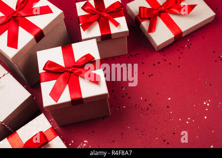 Many present boxes with red bow on red background. Flat lay style. - Stock Photo