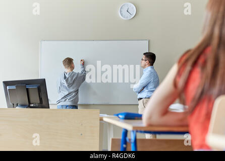 teacher and student writing on board at school - Stock Photo