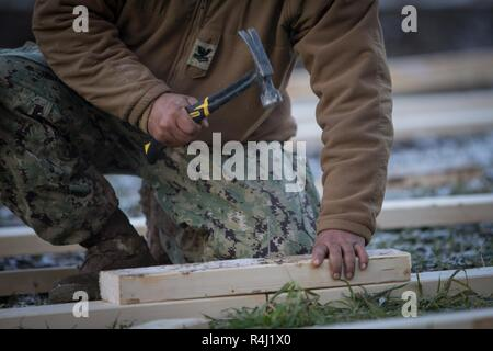 U.S. Navy Utilitiesman 2nd Class Jan Imson with 22nd Naval Construction Regiment builds a riser during Exercise Trident Juncture 18 in Voll, Norway, Oct. 27, 2018. The Seabees constructed risers and walkways throughout the camp to provide dry pathways and areas to work for Combat Logistics Battalion 2 and 2nd Marine Division. Trident Juncture 18 enhances the U.S. and NATO Allies' and partners' abilities to work together collectively to conduct military operations under challenging conditions. - Stock Photo
