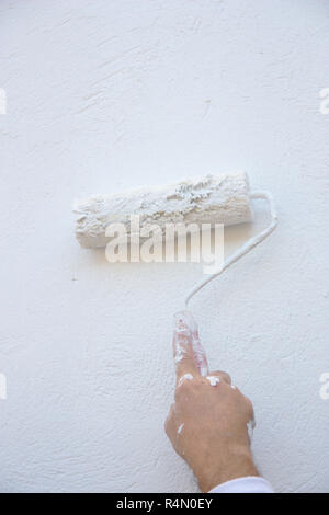 A wall is being painted by the professional painter using a roller with white paint - Stock Photo