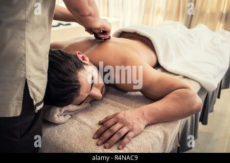 Young man relaxing during traditional massage with hot stones - Stock Photo
