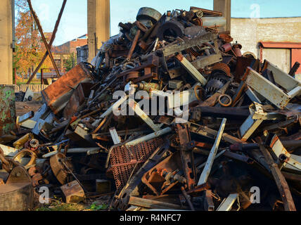 Rusty engines stacked in the scrapyard. Engine parts greased and covered with rust. Dump of pieces of iron and wrecking machinery parts. Scrap yard fo - Stock Photo