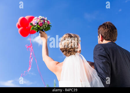 Bride and groom at wedding with helium balloons - Stock Photo