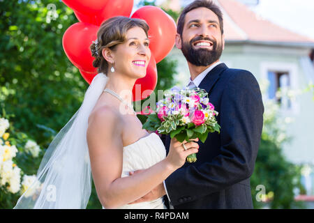 Bride and groom at wedding with read helium balloons - Stock Photo