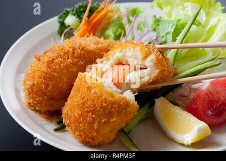 Fried breaded crab meat with cheese on dish - Stock Photo