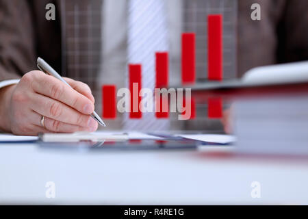 Male arm in suit and tie hold silver pen filling schedule - Stock Photo