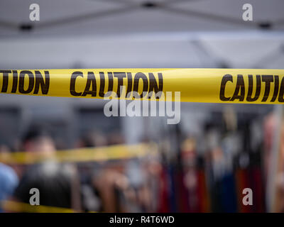 Yellow caution tape, do not enter area, hanging blocking area - Stock Photo