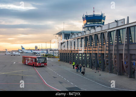 Katowice Airport, Poland - April 26, 2018: People board their plane on the Katowice-Pyrzowice International Airport at sunrise - Stock Photo