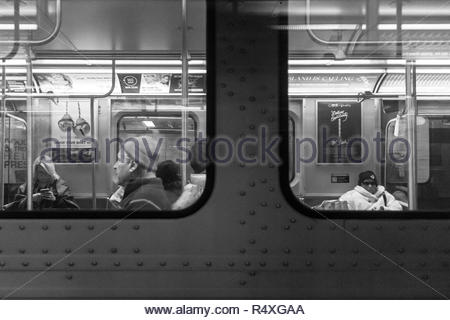 Toronto, Ontario, Canada-November 27, 2018: A view through the windows of a subway train. Everyday lifestyle of real city people as they commute in th - Stock Photo