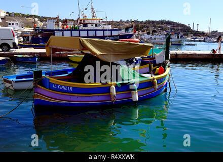 Marsaxlokk, Malta - 7th October 2018:Traditional fishing boats at anchor - Stock Photo