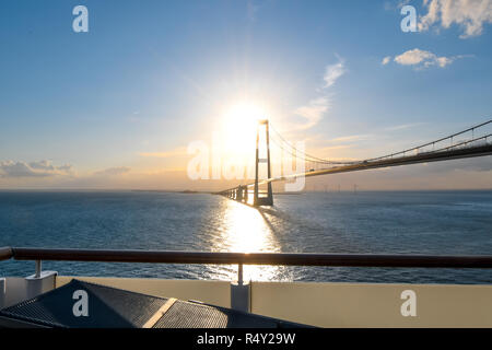 View of the setting sun over the Öresund Bridge which spans the strait between Sweden and Denmark from a boat on the Baltic Sea. - Stock Photo