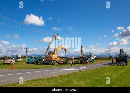 Coalgate, Canterbury, New Zealand - September 27 2018: Power linesmen work on putting up new poles and repairing and improving the power supply - Stock Photo