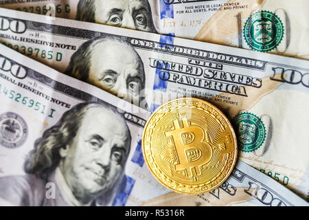 virtual money golden bitcoin on hundred dollars bills background. Exchange bitcoin cash for a dollar. - Stock Photo