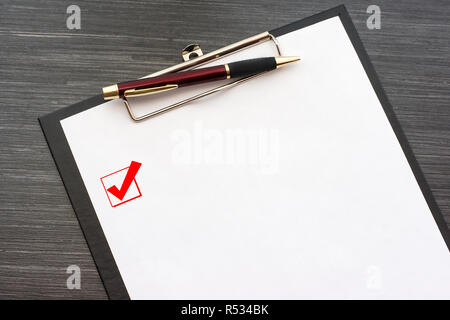 Black clipboard with white sheet of paper and metal pen isolated on dark wooden table. Checkbox with a tick on the page. Top view office accessories - Stock Photo