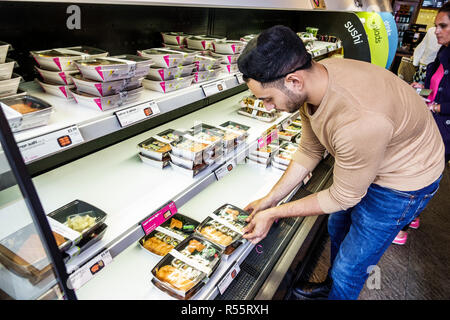 London England United Kingdom Great Britain Westminster Itsu Japanese restaurant take-away prepared packaged fast food sushi refrigerated case man ins - Stock Photo